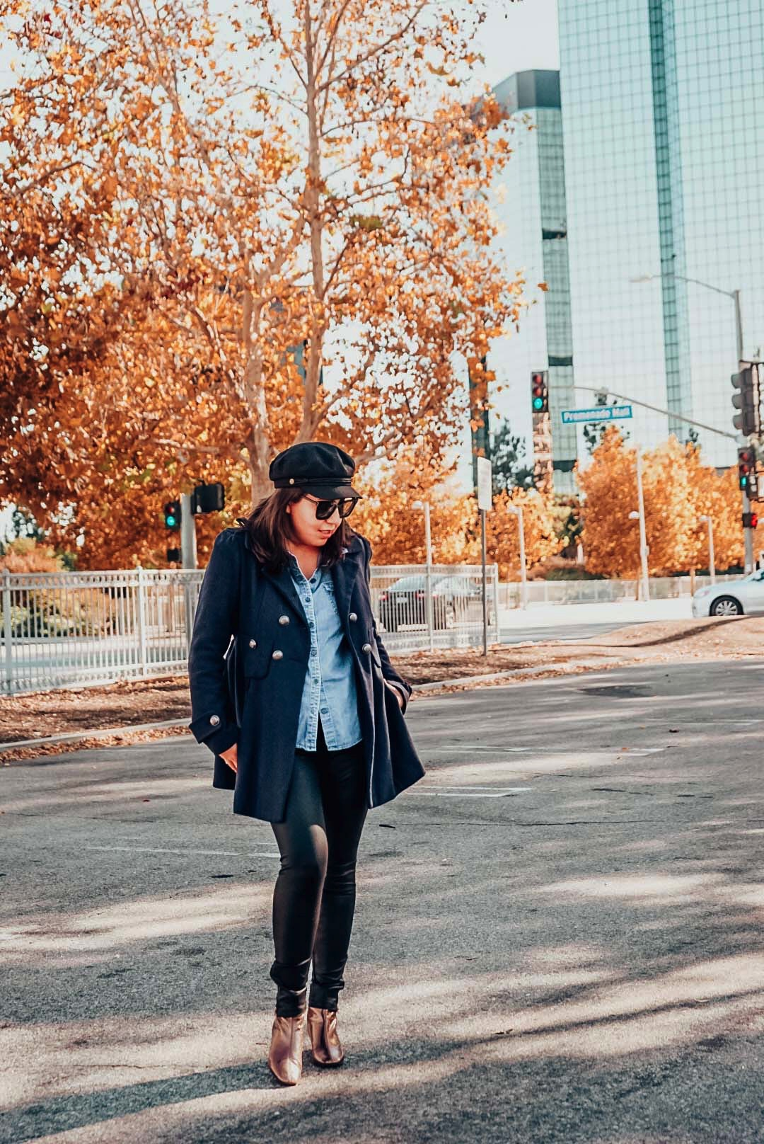 Autumn foliage with a woman wearing navy wool coat, newsboy hat, faux leather leggings, and metallic ankle boots in the city.