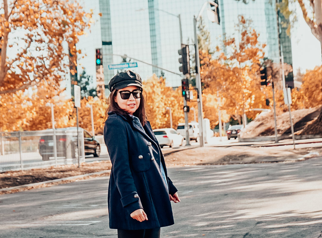 Autumn foliage with a woman wearing navy pea coat, newsboy hat, and metallic ankle boots with faux leather leggings.