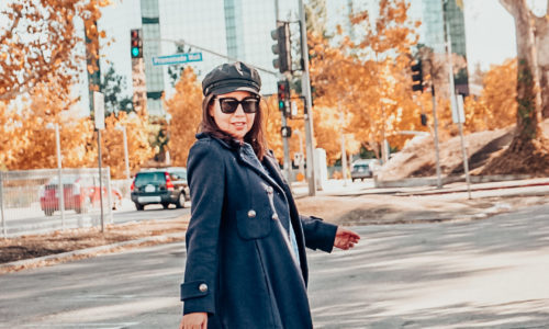 Autumn foliage, and girl in navy peacoat and ankle boots wearing a newsboy hat.