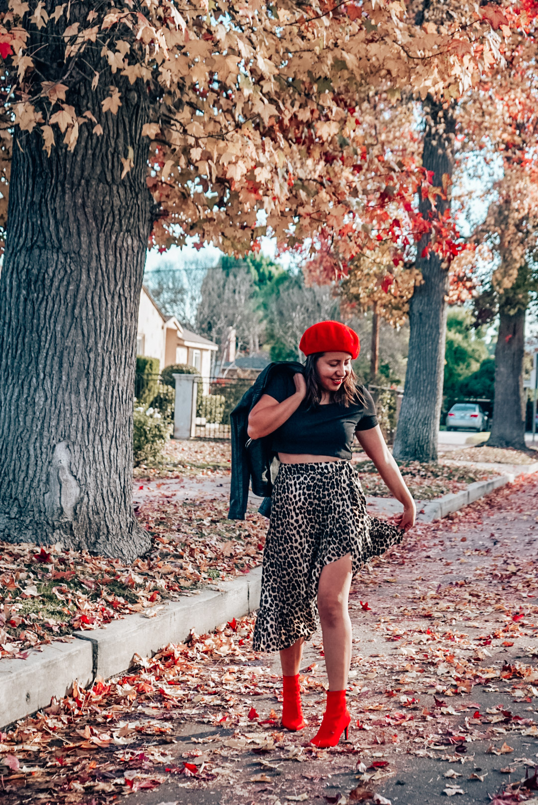A woman wearing leopard print midi skirt and faux leather jacket with red beret and red ankle boots smiling.