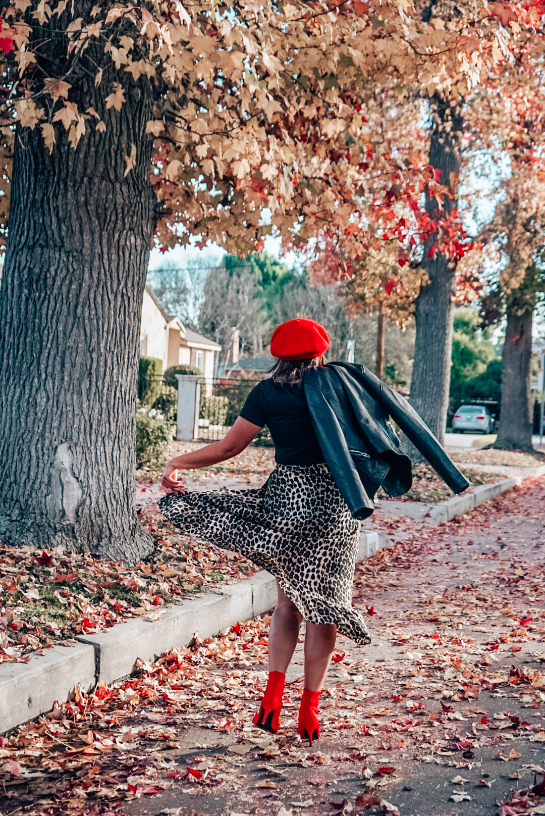 A woman wearing leopard print midi skirt and faux leather jacket with red beret and red ankle boots twirling.