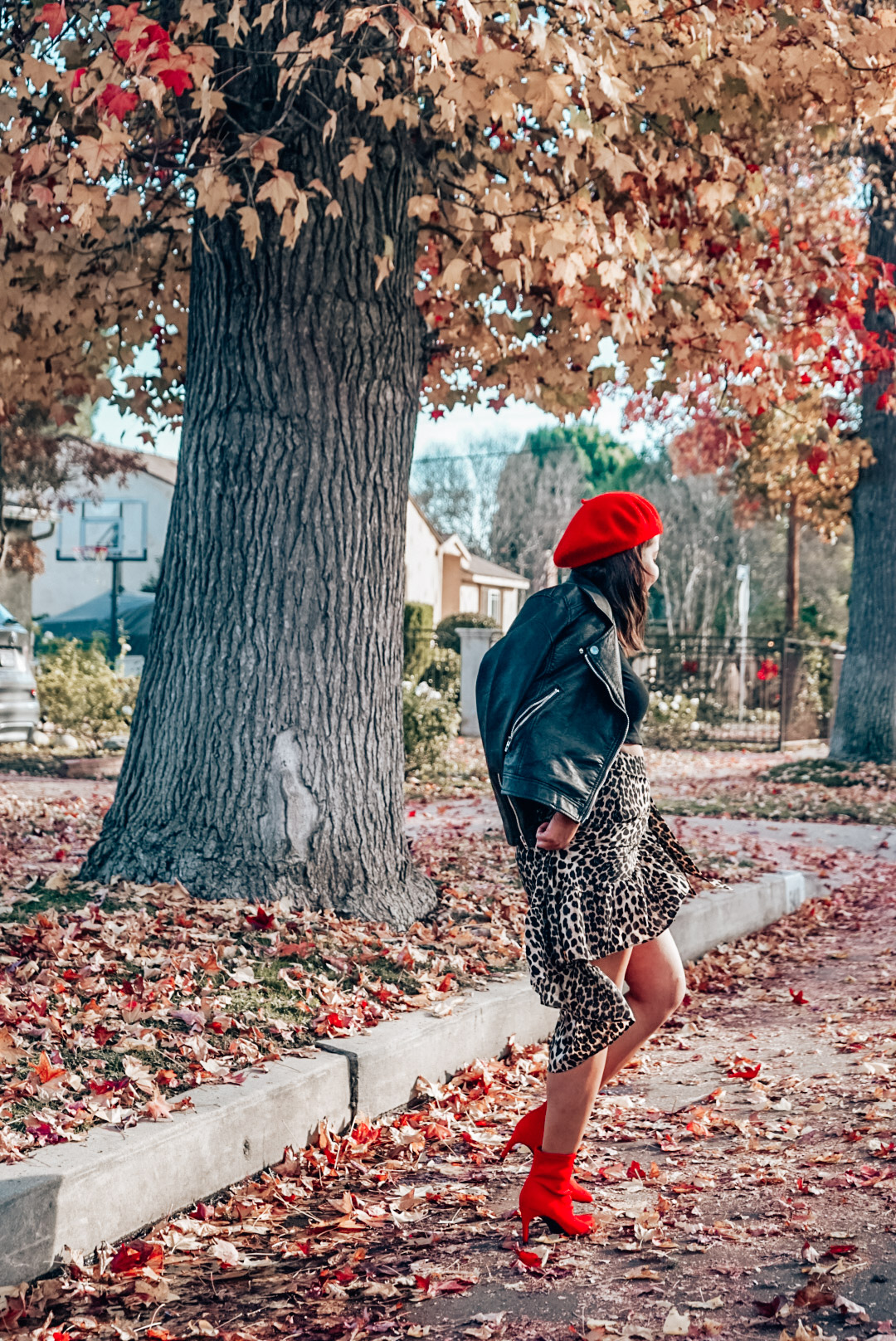 A woman wearing leopard print midi skirt and red beret walking away.