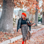Woman dancing in red beret and leopard print skirt with red ankle boots.