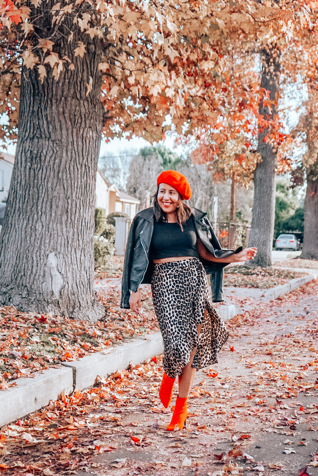 A woman wearing leopard print midi skirt and faux leather jacket with red beret and red ankle boots dancing with one foot in the air.