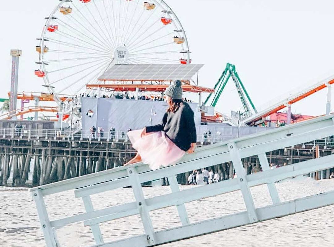 Woman sitting on a lifeguard tower in a tutu in Santa Monica Pier.