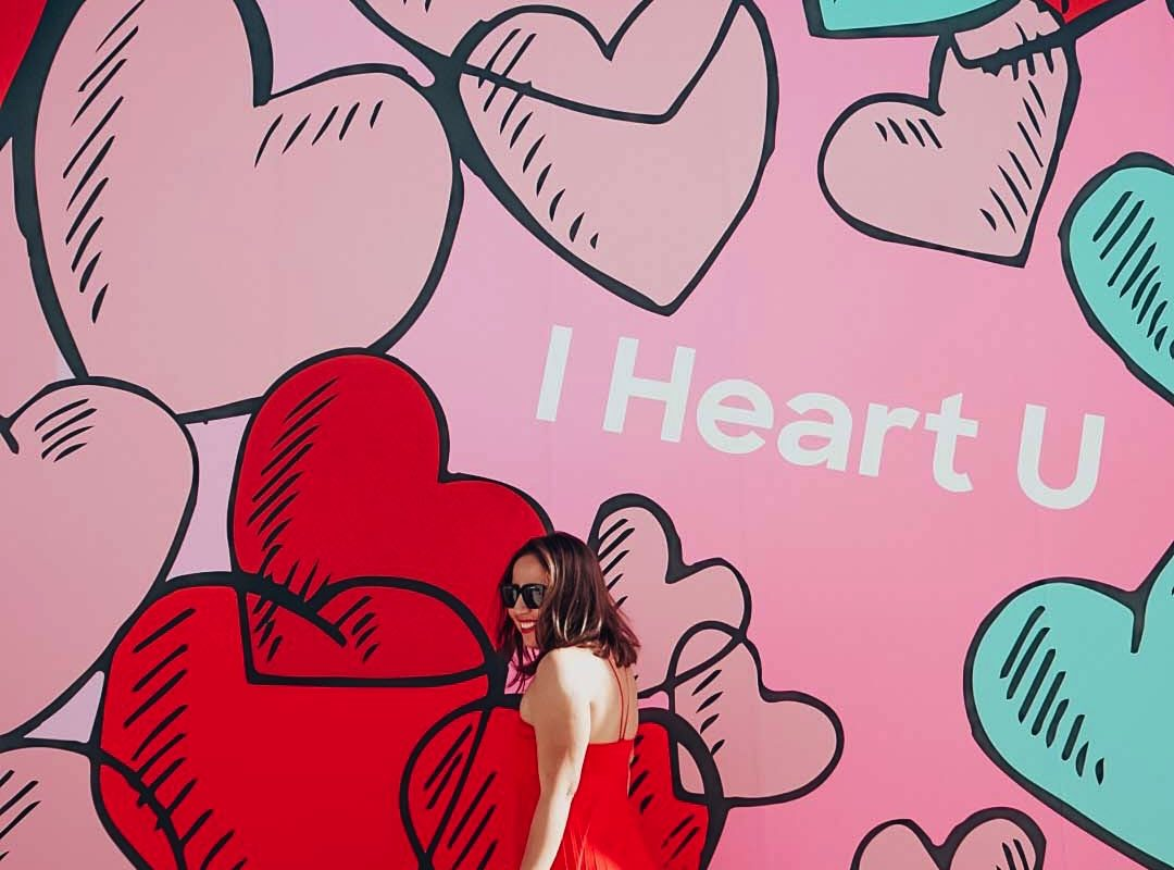 Girl in long red dress with a heart background saying I heart you.