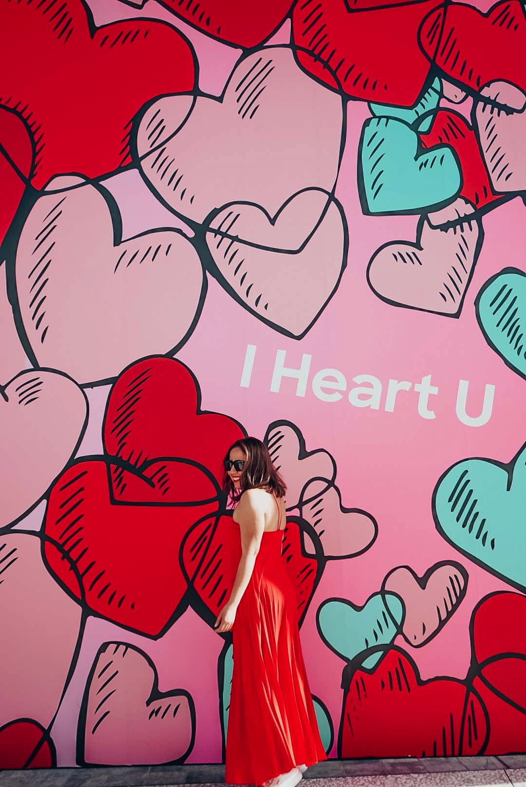 Girl in long red maxi dress strolling in front of a heart mural in Los Angeles.
