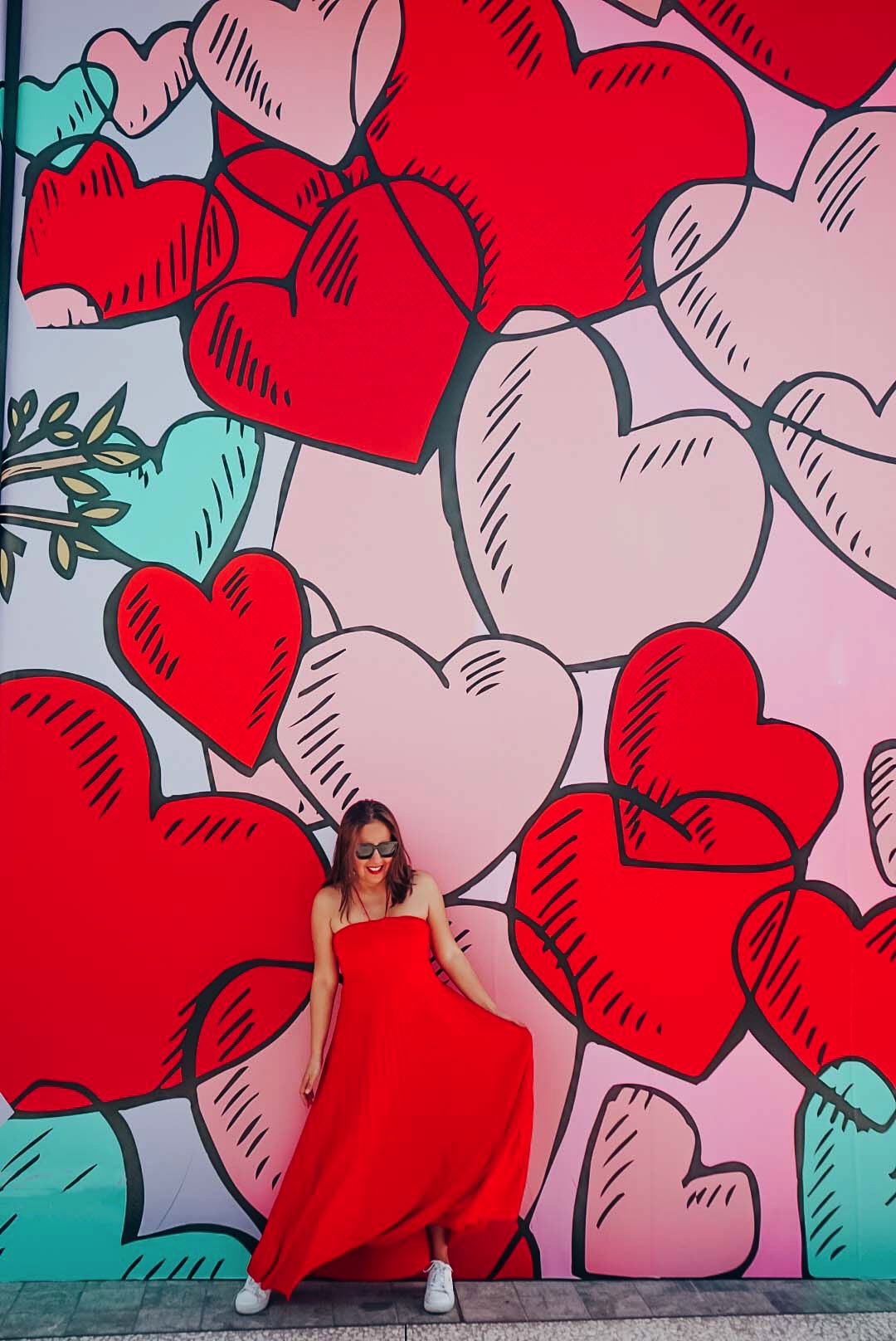 Girl in long red maxi dress against a heart mural.