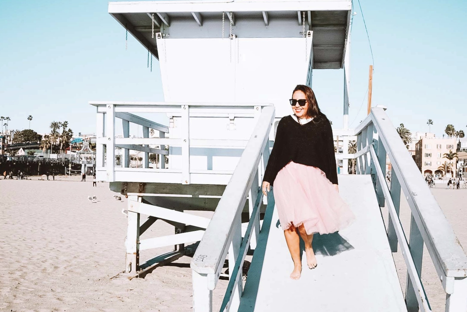 Woman in a pink tutu at the beach smiling wearing sunglasses waling down a lifeguard tower.