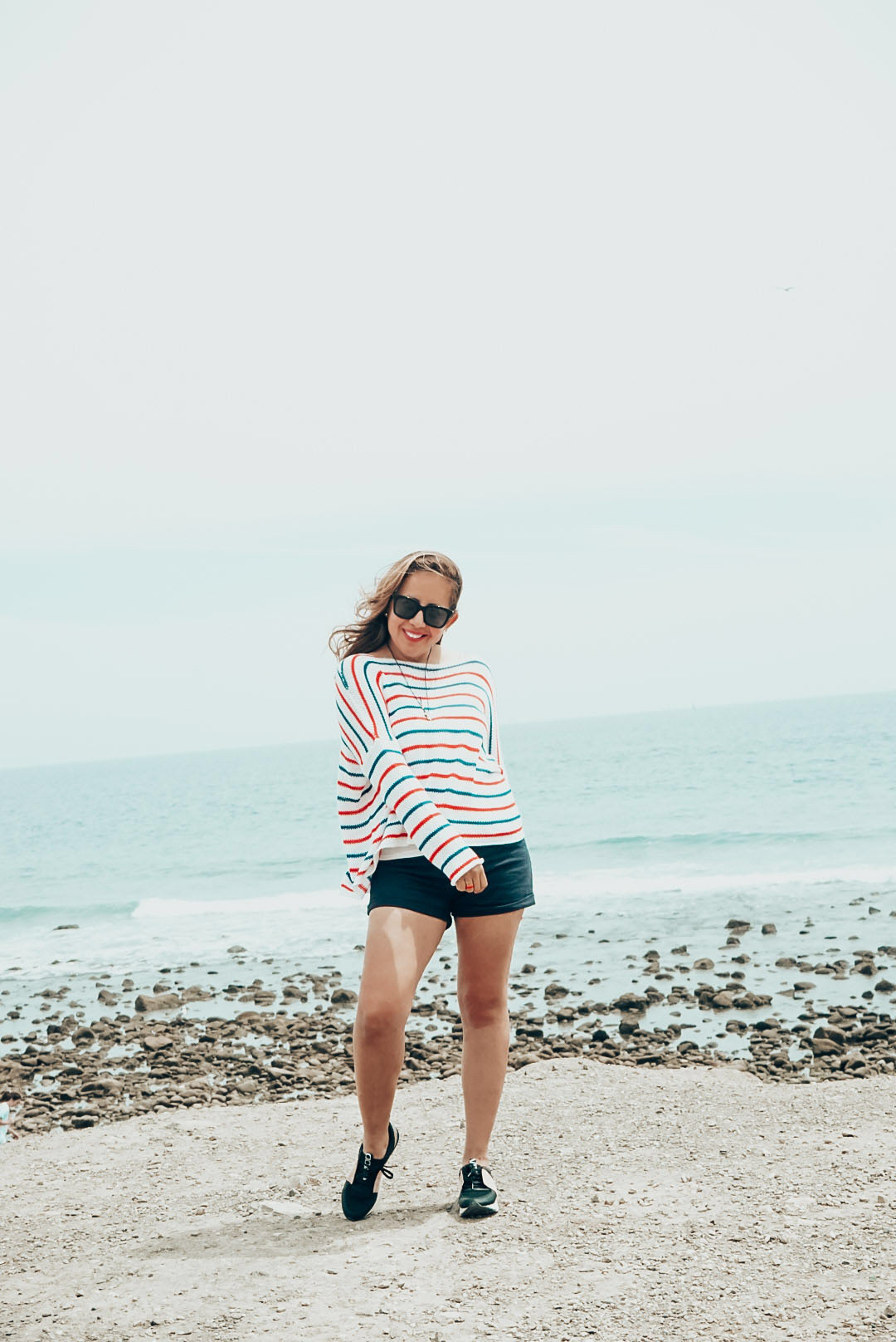 Girl in red white and blue knit sweater at the beach.