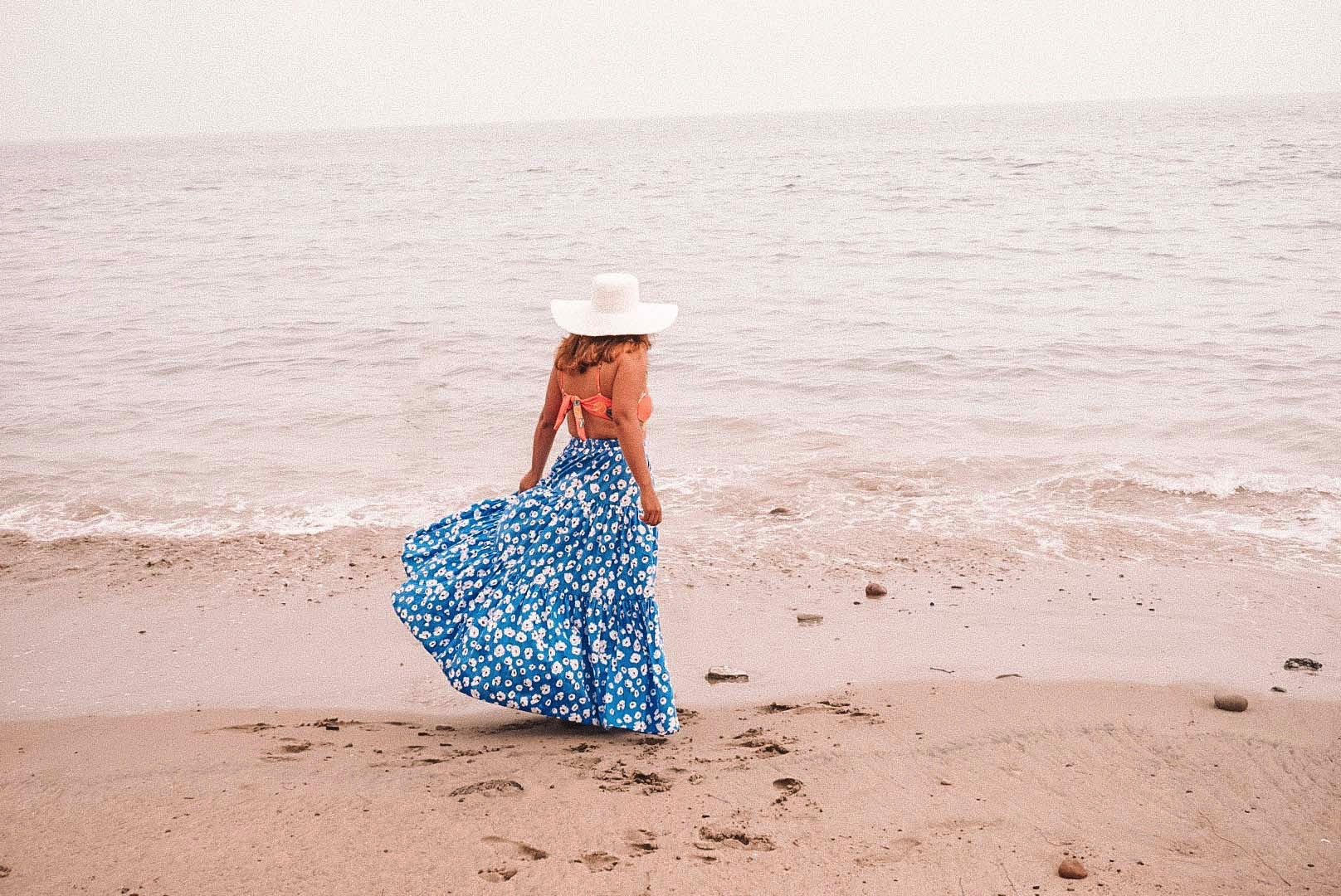Woman in long tiered blue floral printed skirt at the beach.