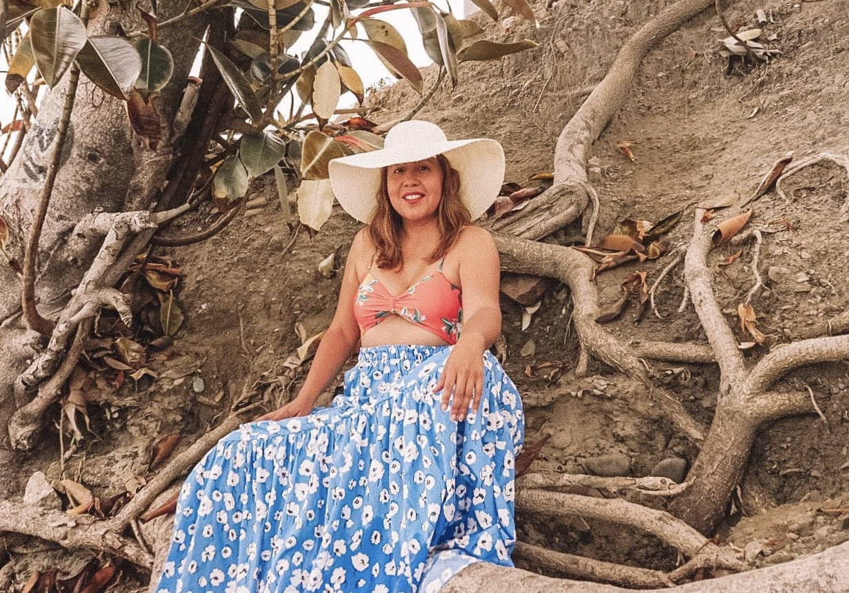 Cutout bathing suit top and long tiered skirt are styled perfectly with a floppy hat.
