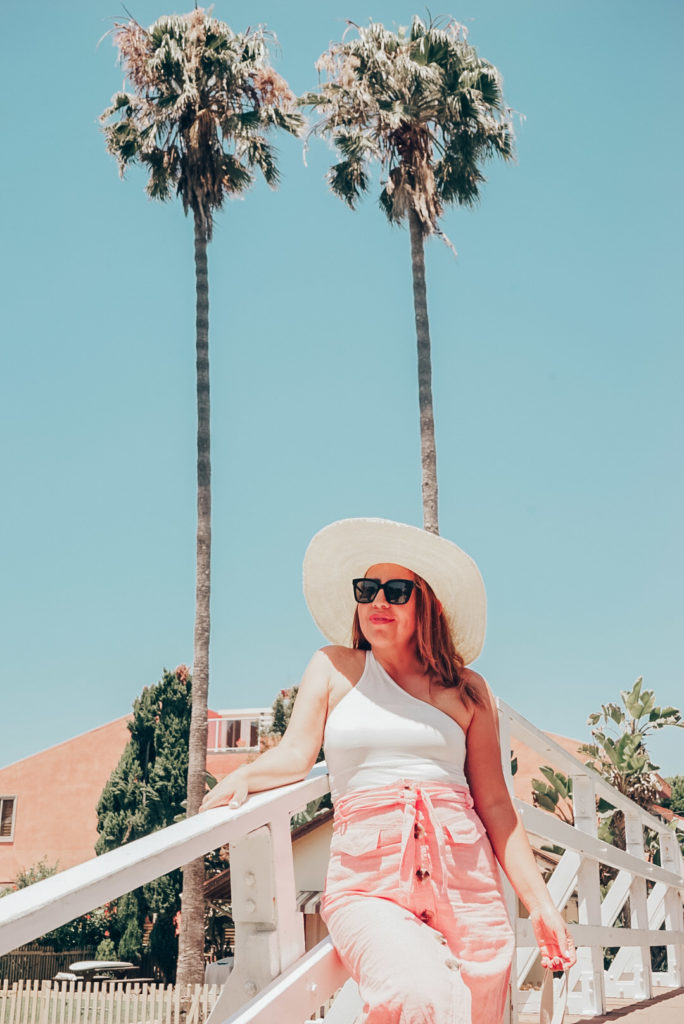Girl in Los Angeles wearing one shoulder top and button front midi skirt standing in front of palm trees.