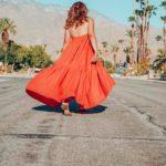 Girl in long orange dress walking in Palm Springs.